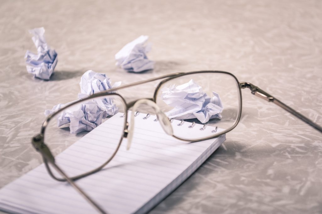 close up of glasses surrounded by balled up paper